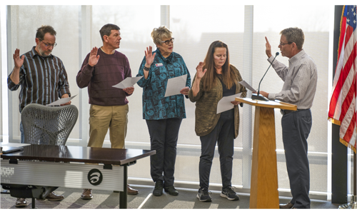 Four elected board members hold up their hands to be sworn in by Dr. Greg Joyce.