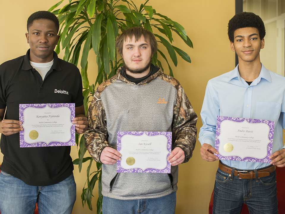 Butler students hold their PBL stock market awards.