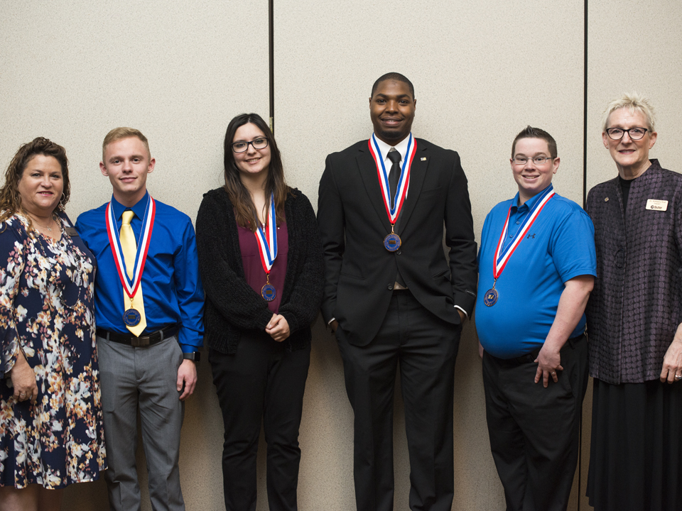 Butler students pose with their medallions, standing with their advisor and the president.