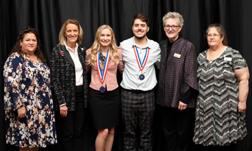 Butler students pose with their medallions, standing with their advisors, the college president and a Kansas House of Representatives member.