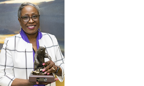 Junetta Everett poses with her grizzly bear statue for the Distinguished Alumna award.