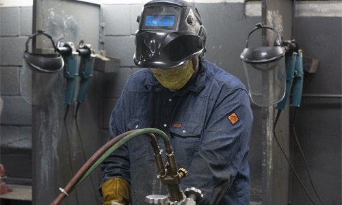A welding student wears a mask while cutting metal.