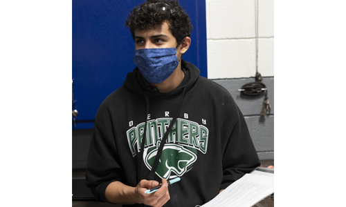 Automotive Technology student listens to instructor with mask.