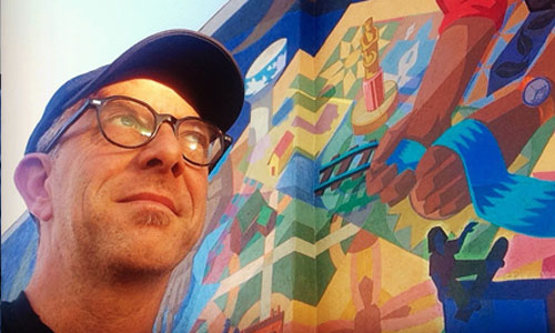Dave Loewenstein in front of a mural.