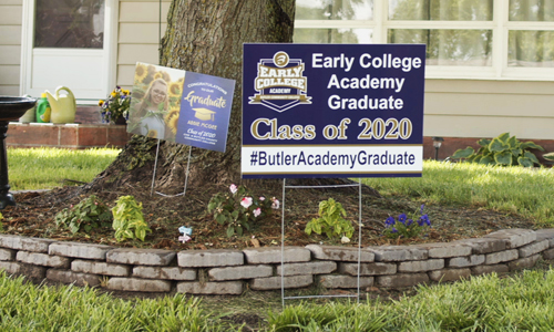 An Early College Academy sign stands in a graduate's yard.