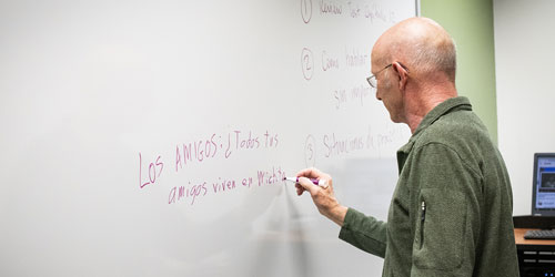 Foreign Language student working on Spanish sentence structure by writing on a white board during class near Wichita at Butler Community College