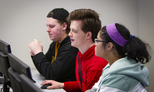 Students work together in front of computers during a cybersecurity class.