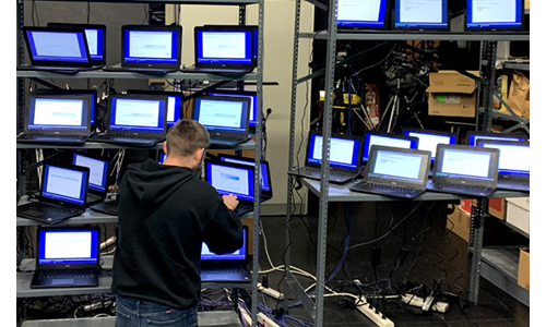 A Butler information services worker configures shelves full of laptops.