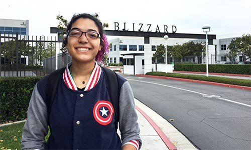 Jacquelyn Washington stands in front of the entrance to Blizzard Entertainment.