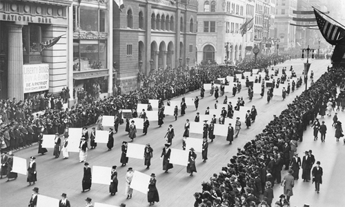 Groups of women march down a street, holding banners during a parade.