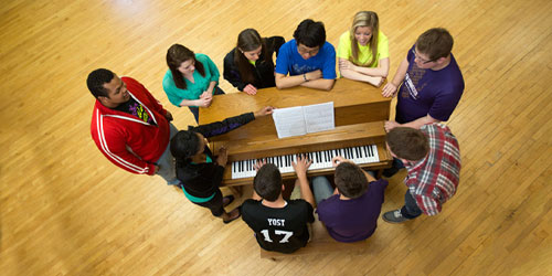 Vocal music students around a piano near Wichita at Butler Community College