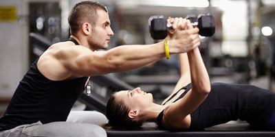 Man training a woman how to do a chest fly