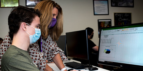 Business medical specialist student at computer with instructor